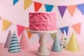 fuoco selettivo di torta di compleanno rosa deliziosa con la candela sulla torta stand vicino partito tappi e decorazione
