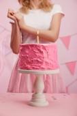 oříznutý pohled ženy stojící poblíž Servírovací stojan s chutné růžové narozeninový dort a hořící svíčka