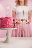 Selektivní fokus lahodné narozeninový dort na Servírovací stojan u ženy na růžové