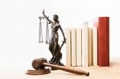 figurina con scale di giustizia, marrone martelletto e libri sulla tavola di legno isolato su bianco