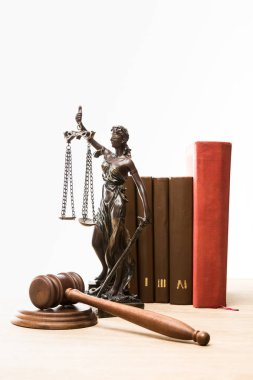 figurine with scales of justice, gavel and books on wooden table isolated on white