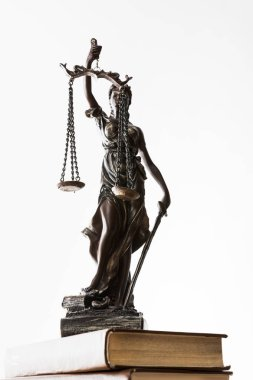 bronze figurine with scales of justice on brown books isolated on white