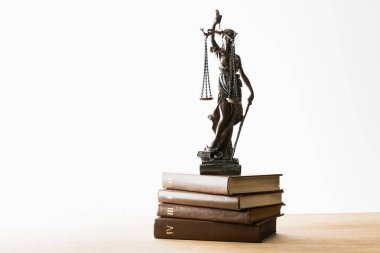 bronze figurine with scales of justice on pile of brown books on wooden table isolated on white