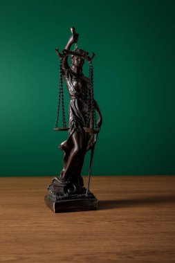 bronze statuette with scales of justice on wooden surface on green background