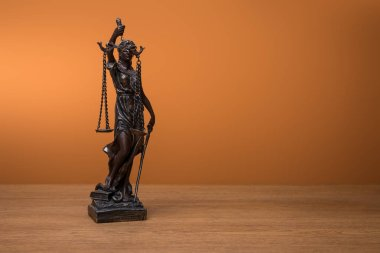 bronze statuette with scales of justice on wooden table on orange background
