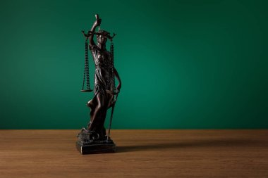 bronze statuette with scales of justice on wooden table on dark green background