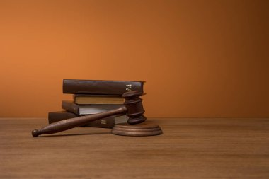 volumes of brown books in leather covers and gavel on wooden table on dark orange background