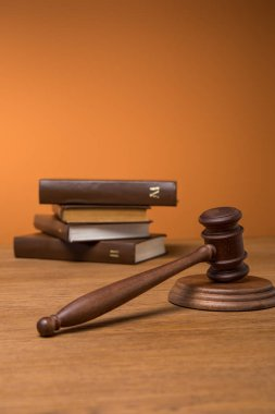 selective focus of volumes of brown books in leather covers and gavel on wooden table on orange background
