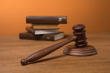 selective focus of volumes of brown books in leather covers and wooden gavel on table on orange background