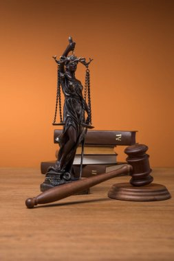 bronze statuette with scales of justice, gavel and books on wooden table on orange background