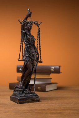 selective focus of bronze statuette with scales of justice and volumes of brown books on wooden table