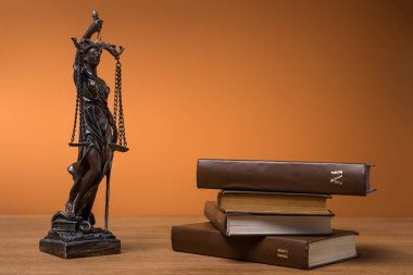 bronze statuette with scales of justice and volumes of brown books on table