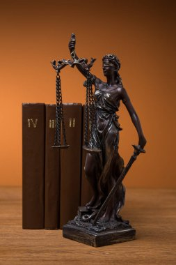 bronze statuette with scales of justice and row of brown books on wooden table