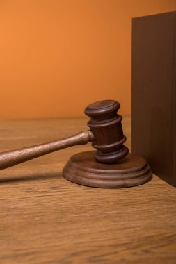 close up of brown book in leather cover and gavel on wooden table isolated on orange