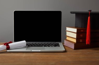 Laptop with blank screen, books, diploma and academic cap on wooden table isolated on grey