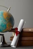 Hnědé knihy, glóbus a diplom s červenou stuhou na šedé