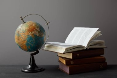 Old globe and books on dark surface on grey stock vector