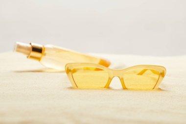 Selective focus of yellow sunglasses near suntan oil bottle on sand isolated on grey stock vector