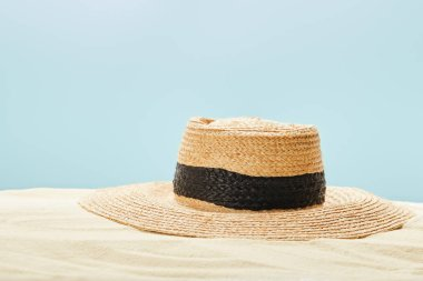Selective focus of straw hat on sandy beach in summertime isolated on blue stock vector