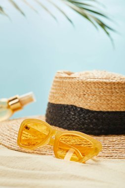 Selective focus of sunglasses near straw hat and bottle with suntan oil on sandy beach isolated on blue stock vector
