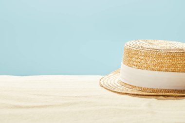 selective focus of straw hat on sandy beach in summertime isolated on blue