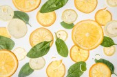 Photo bright orange and lemon slices with green spinach leaves on grey background