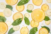 Fotografie jasně oranžová a plátky citronu s listy špenátu na šedém pozadí
