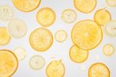 světlé čerstvé pomeranče a plátky citronu na šedém pozadí