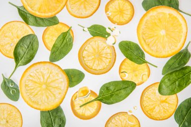Juicy orange slices with green spinach leaves on grey background stock vector