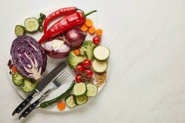 Top view of cutlery and fresh vegetables on white surface