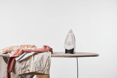 Clothes and iron on ironing board isolated on grey