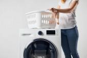 Teilansicht einer Frau mit Wäschekorb und Waschmaschine isoliert auf grau