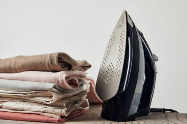 Iron and folded ironed clothes on ironing board isolated on grey