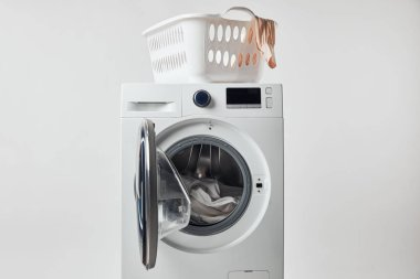 Washing machine with laundry basket isolated on grey