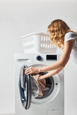 Partial view of curly woman putting clothes in washing machine isolated on grey stock vector