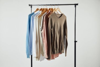 Straight rack, wooden hangers and male clothes isolated on grey