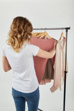Back view of girl hanging hangers with clothes on straight rack on grey