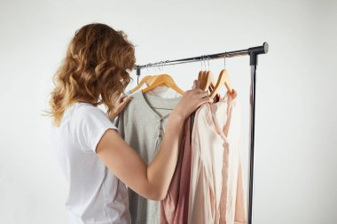 Back view of girl hanging hangers with clothes on straight rack on grey stock vector