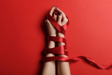 cropped view of woman tied with satin ribbon on red background