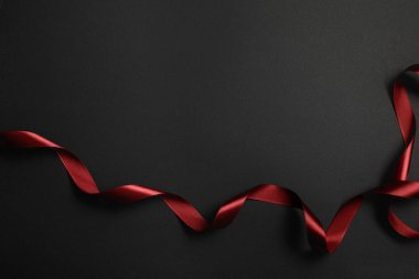 Top view of red silk wavy ribbon on black background with copy space stock vector