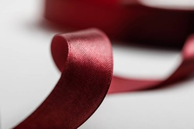 selective focus of shiny silk curved burgundy ribbon on grey background