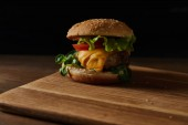 fresh tasty meat burger with cheese and greenery on wooden chopping board isolated on black
