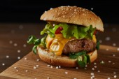 close up of tasty meat burger with salt on wooden chopping board