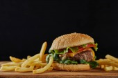 delicious meat burger with cheese, greenery and sesame near french fries isolated on black