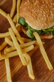 delicious burger with greenery and sesame near french fries on wooden surface