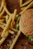 top view of delicious burger with sesame on bun and french fries with salt