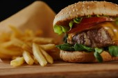 selective focus of delicious burger with meat and french fries on wooden surface