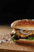 seasoning and delicious burger with meat, cheese and onions isolated on black