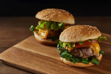 tasty meat burgers with melted cheese on wooden chopping board