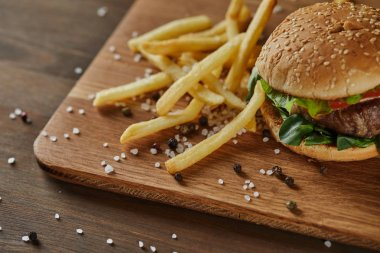 fresh golden french fries with tasty meat burger with scattered salt and black pepper on wooden chopping board